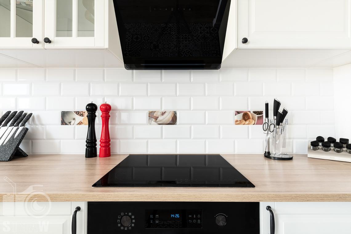 Sesja fotograficzna mieszkania na sprzedaż, zdjęcia nieruchomości po remoncie i w pełni wyposażonej, płyta grzewcza, piekarnik i okap w kuchni.
