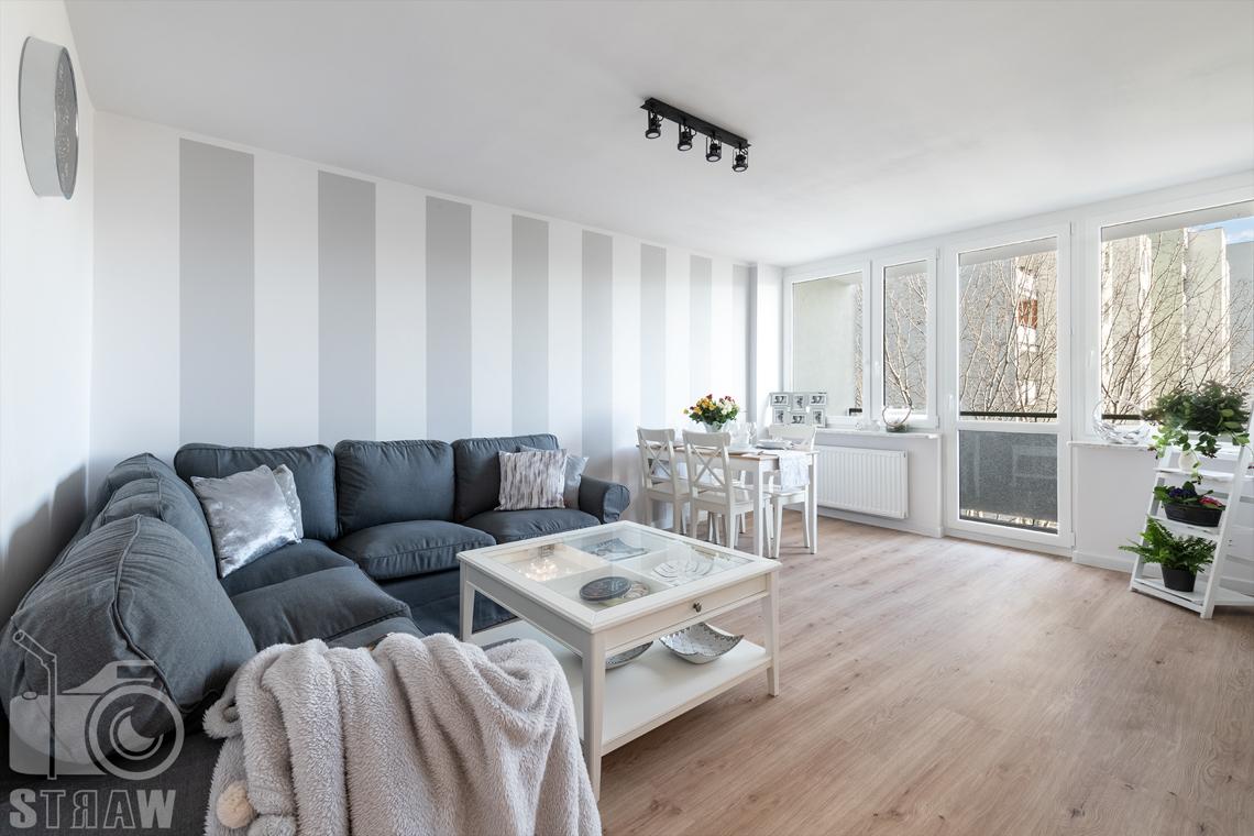 Sesja fotograficzna mieszkania na sprzedaż, zdjęcia nieruchomości po remoncie i w pełni wyposażonej, salon z dużą sofą i białym stolikiem kawowym.